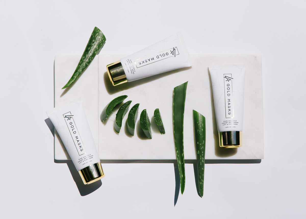 LA Gold Masks Product on white marble with aloe vera slices